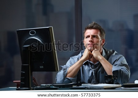 Determined businessman concentrating hard on difficult computer task working late in office looking worried.?