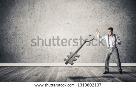 Determined businessman in concrete interior breaking with fist stone key figure #1310802137