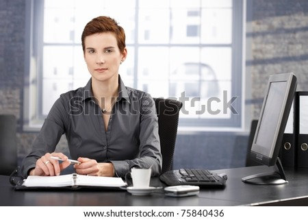 Determined businesswoman sitting at desk, working with personal organizer, looking at camera.?