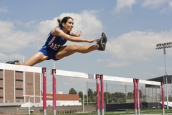 Determined female athlete jumping over a hurdles