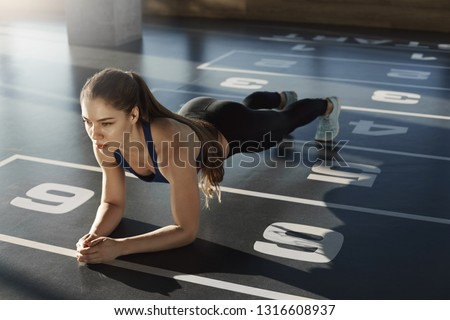 Determined fit focused female fitness coach standing in plank feeling endurance exercising alone in sports club, working-out in gym wearing activewear sports-bra leggings, build perfect body shape