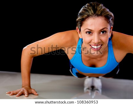 Determined fit woman exercising by doing push-ups