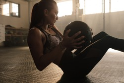 Determined fitness woman exercising with pilates ball at  healthclub. Female doing workout using medicine ball.