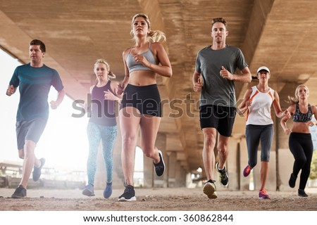 Determined  group of young people running together in city. Low angle shot of running club members training together in morning under a bridge.