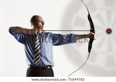 Determined handsome businessman aiming at target with bow and arrow, isolated on white background.