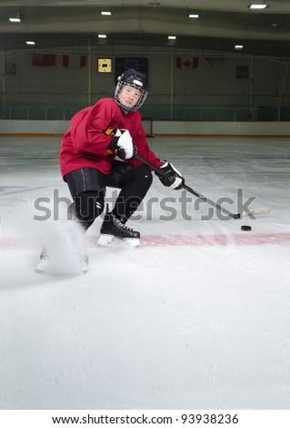 Determined Hockey Player Sprays Ice as he Makes Sharp Stop on Skates