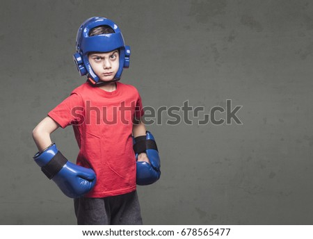 Determined little fighter wearing gloves and helmet. Martial arts kids concept #678565477