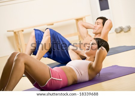 Determined man and woman doing stomach crunches in health club