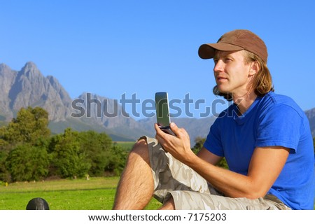 Determined man sits on grass with his phone/pda/gps and looks far - and misty mountains are background. Shot in Stellenbosch, South Africa. - stock photo