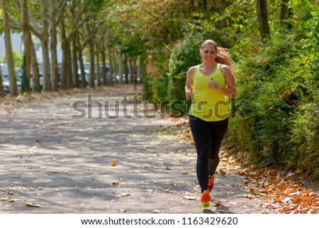 Determined middle-aged woman jogging during cardio workout for burning calories outdoors in the park in Autumn #1163429620