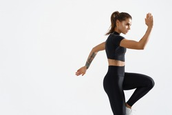 Determined muscular female athlete workout, raising leg and doing stretching exercises. Sport woman in sportswear training indoors, doing fitness aerobics, white background.