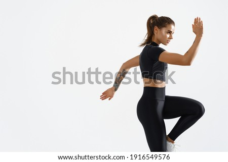 Determined muscular female athlete workout, raising leg and doing stretching exercises. Sport woman in sportswear training indoors, doing fitness aerobics, white background. Photo stock ©
