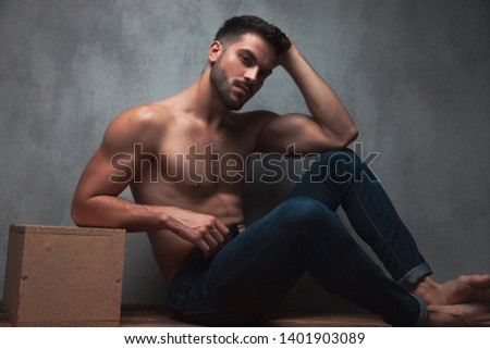Determined shirtless sexy man looking to the camera and holding one o his hands on his head while leaning on a box and sitting on gray studio background