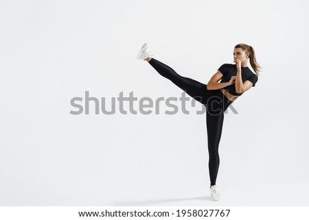 Determined sport woman in activewear do high kick, tae-bo martial arts exercises isolated on white background. Athletic fit girl with perfect body kick air, punching with legs, practice kicks
