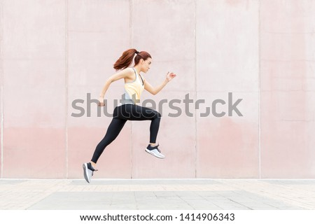 Determined sporty woman in jogging by building in city