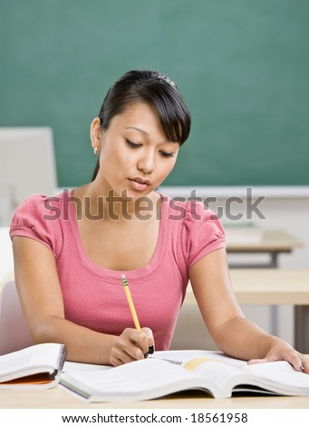 Determined student doing homework from text book