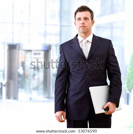 Determined successful businessman standing and holding laptop computer in hand, outdoor in front of office building.