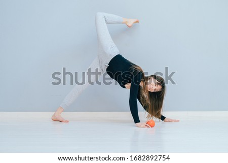 Determined to win. Modern young playful happy brunette woman in sport clothing crouching workout buttocks exercise in pilates studio over grey wall background.