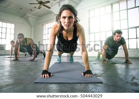 Determined woman conviction strength coach fitness workout training with coed class