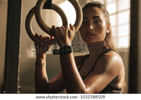 Determined woman exercising with gymnastic rings in gym. Sportswoman standing at  gym holding dip rings. #1031588509