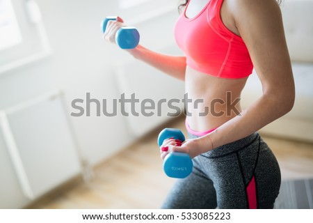 Determined woman losing weight at home and exercising with dumbbells