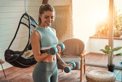 Determined woman losing weight at home and exercising with dumbbells. Sport and recreation concept. Beautiful woman in sportswear with blue dumbbells in her hands.