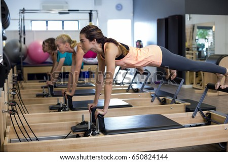 Determined women practicing stretching exercise on reformer in gym #650824144