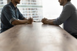 Determined young businessmen sit opposite at desk face each other talk speak at business meeting or negotiations. Male rivals or opponents have briefing in office. Rivalry, confrontation concept.