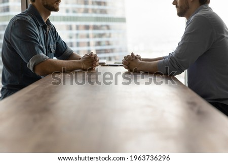 Determined young businessmen sit opposite at desk face each other talk speak at business meeting or negotiations. Male rivals or opponents have briefing in office. Rivalry, confrontation concept. Foto stock ©