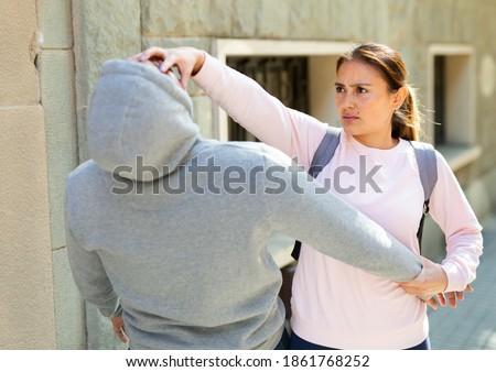 Determined young Latina using Krav Maga techniques to protect herself from attacker man on city street. Female self-defense concept.. Stock fotó ©