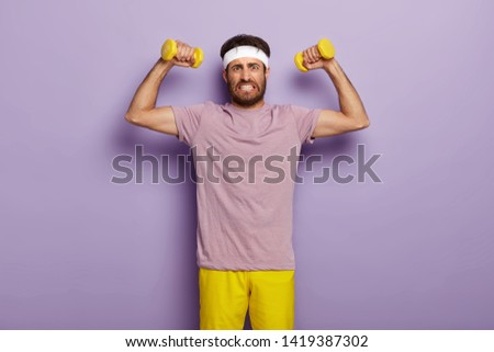 Determined young sporty unshaven man clenches teeth, raises muscular arms, does exercises with dumbbells, clenches teeth, wears white headband, t shirt and shorts, isolated over purple background.