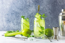 Detox cocktail with mint, cucumber and lime or mojito cocktail in highball glasses on a gray concrete stone surface background. With copy space for your text