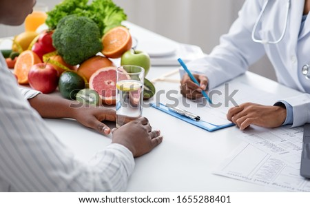Detox concept. Afro woman patient of nutritionist drinking lemon water while doctor taking notes, close up