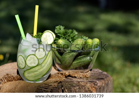 Detox cucumber diet drink. Healthy summer cooler on tree stump.  Cold fresh lemonade with cucumber and ice, selective focus. Refreshing cucumber cocktail, lemonade, detox water in a glass.  #1386031739