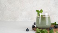 Detox drink. Glass of healthy refreshing chlorella spirulina smoothie with mint, blueberries, yogurt and spirulina powder. Summer vitamin refreshing drink. Healthy diet. Superfood. Copy space.