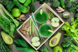 Detox green smoothies concept, two glasses of green diet detox drink  and various fresh green vegetables around them, view from above composition