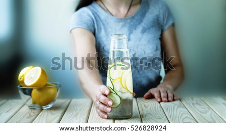 Detox. healthy eating, drinks, diet, detox and people concept - close up of woman with fruit water in glass bottle