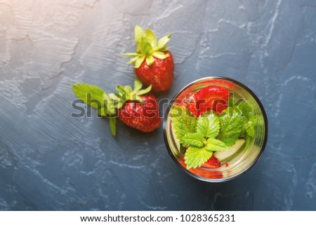 Detox water with strawberry and cucumber in glass on the dark background. Top view. Copyspace.