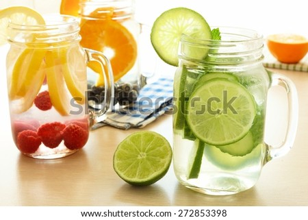 Detox water with various types of fruit in mason jars on a table