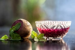 Detoxifying Beetroot extracted tincture in a glass bowl on black glossy surface with some raw fresh sliced beetroot vegetable with it used as a remedy for Inflammation in the kidney. Horizontal shot.