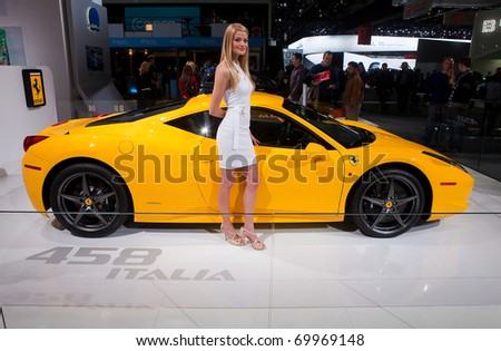 DETROIT - JANUARY 13: A model poses with a Ferrari 458 Italia at the 2011 North American International Auto Show Industry Preview on January 13, 2011 in Detroit, Michigan.