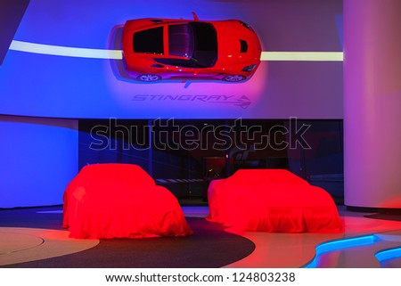 DETROIT - JULY 14 : Vintage Corvettes sit under covers at the 2014 Chevrolet Corvette unveiling January 14, 2013 in Detroit, Michigan. - stock photo