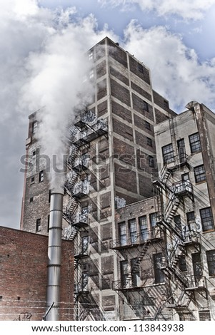 Detroit Michigan city view. There is an old building with graffiti and a fire escape along it's side. There is a steam pipe in front creating an eerie feel. #113843938