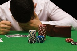 Devastated gambler man losing a lot of money playing poker in casino, gambling addiction. Divorce, loss, ruin, debt, ludopata concept