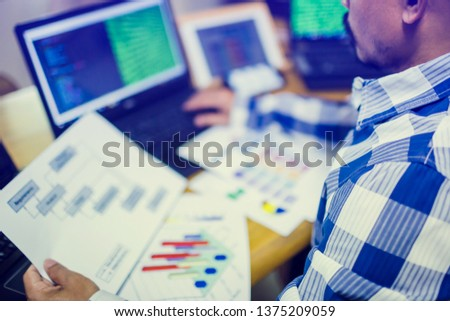 developer is designing software on paper chart with multi computer and tablet, developing programming and coding technologies, website design, the concept of cyber space and system design.