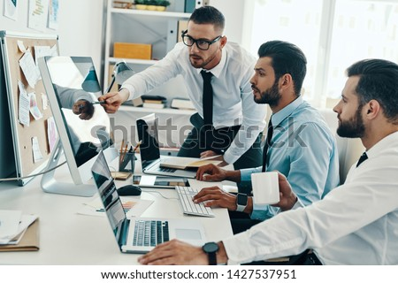 Developing new approaches. Group of young modern men in formalwear working using computers while sitting in the office