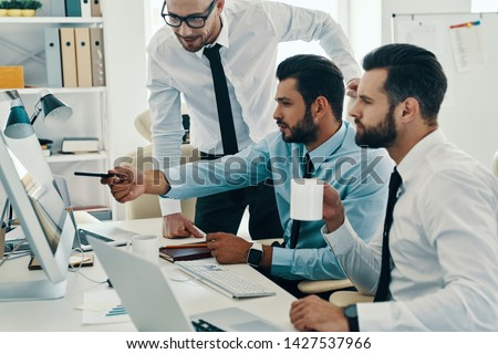 Developing new strategy. Group of young modern men in formalwear working using computers while sitting in the office