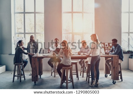 Developing new strategy. Modern young man conducting a business presentation while standing in the board room #1290805003