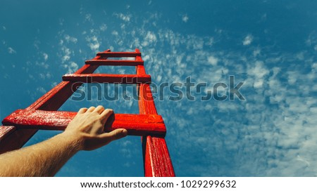Photo of  Development Attainment Motivation Career Growth Concept. Mans Hand Reaching For Red Ladder Leading To A Blue Sky