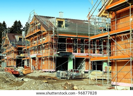 Development construction site with 3 houses in scaffolding